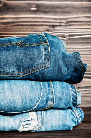 slacks: fashionable clothes. pile of jeans on a wooden background