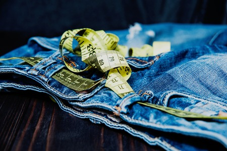centimeter: jeans and centimeter on a wooden background. clothing Stock Photo