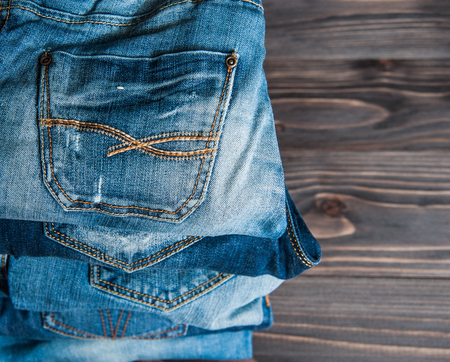 slacks: stack of various shades of blue jeans on a wood background
