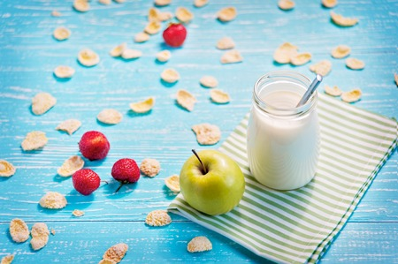 scatter: Jar of milk and green apple in the striped napkin on the table. Corn flakes with strawberry scatter.