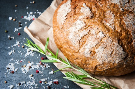 chignon: A loaf of bread with rosemary salt and pepper on paper closeup Stock Photo