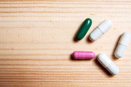 antibiotic capsule: Drug prescription for treatment medication. Pharmaceutical medicament, cure in container for health. Pharmacy theme, Heap of green pink white round capsule pills with medicine antibiotic in packages. Stock Photo