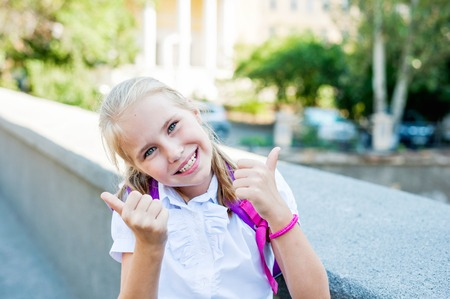 Schoolgirl in school uniform showing thumbs up. Back to school, happy childhood, successful concept.