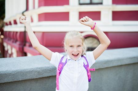 Schoolgirl in school uniform showing hands up. Back to school, happy childhood, successful concept. Stock Photo