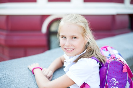 Little beautiful smiling girl with backpack on a background city street.
