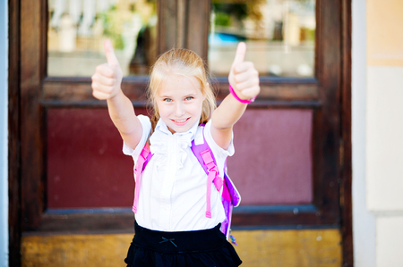 Schoolgirl in school uniform showing thumbs up. Back to school, happy childhood, successful concept. Selective focus