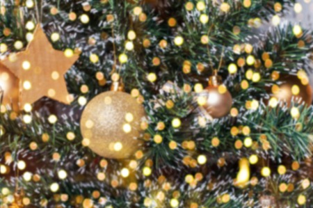 glitzy: Christmas golden balls ornaments on blured fir tree closeup with gold bokeh Stock Photo