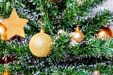 glitzy: Christmas golden ornaments on fir tree closeup