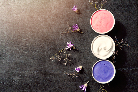 revitalizing: Purple spa setting on old black stone table - cream or mask in little cup with dry flowers around Stock Photo
