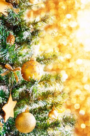 glitzy: Christmas golden balls ornaments on fir tree closeup with gold bokeh