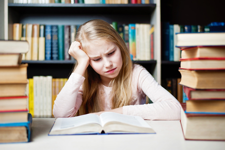 Angry and tired schoolgirl studying with a pile of books on her desk Stock Photo - 69369440