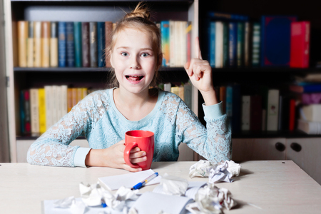 Young blond girl having an idea sitting at the desk with cup of tea in hand and crumpled paper on the tablr