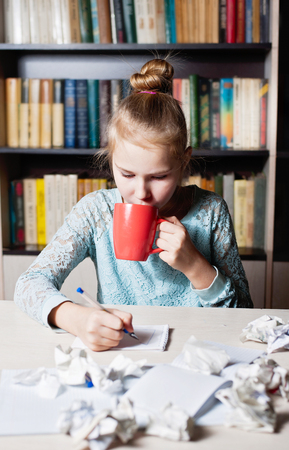 Beautiful young girl sitting on workplace with crumpling the sheet and drinking tea Stock Photo