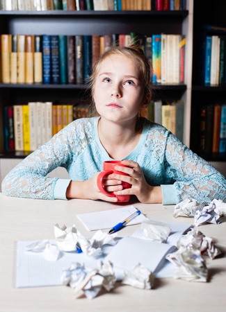 disconcert: Young girln with writers block staring thoughtfully with cup of tea off to the side with a large heap of crumpled discarded paper on her desk.