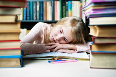 tired student girl with books sleeping on the table. education, session, exams and school concept . studying hard.