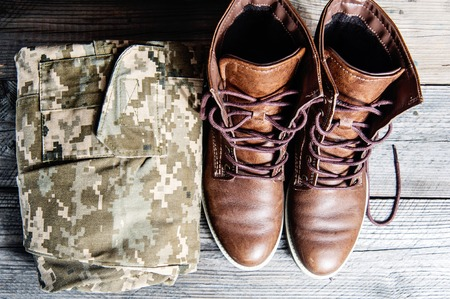 clothe: military uniform boots and cloth on Wooden floor Stock Photo
