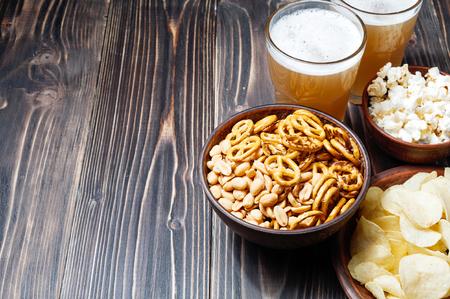 Bier mit Brezeln, Saltsticks und Kartoffelchips auf hölzernem Hintergrund. Von oben mit copyspace betrachtet Standard-Bild - 78070115