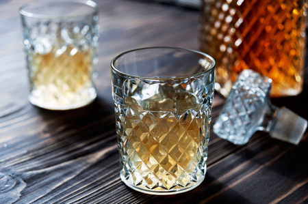snifter: Crystal Decanter. Crystal glasses. Brandy, cognac whiskey with ice closeup