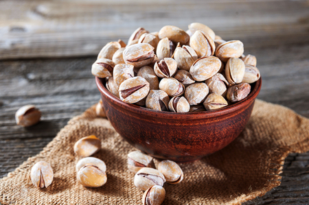 Pistachios in wooden bowl over napkin on wooden background, selective focus.