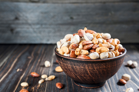 Nuts set in bowl almonds, pistachios, cashews, peanuts, vintage wooden background with copyspace Stock Photo