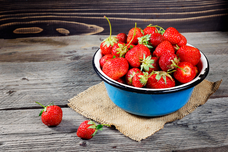 harvested: Red berry strawberry in metal mug on rustic wooden background. Background from freshly harvested strawberries.