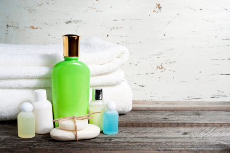 articles: Bathroom accessories and white towel. Soap and lotion. Beauty care accessories for bath. White background. Copy space.