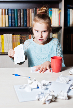 Stressed angry girl at the table, in hands crumpling a piece of paper