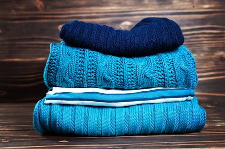 Knitted wool sweaters. Pile of knitted winter, autumn clothes on wooden background, sweaters, knitwear, space for text.