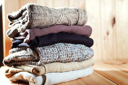 Pile of knitted winter clothes on wooden background, sweaters, space for text, selective focus