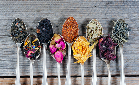 Various kinds of tea in spoons on wooden background. Dry Tea assortment.