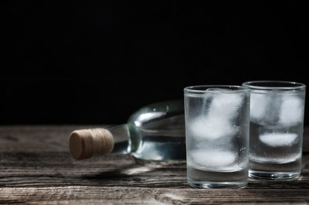 Cold vodka in shot glasses on a black background on wooden table