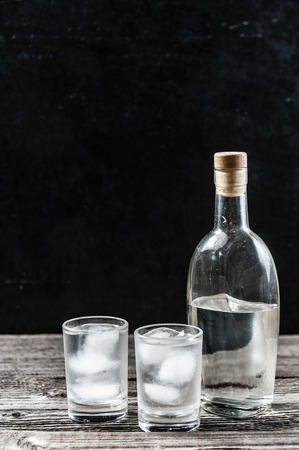 Cold vodka in shot glasses on a black background on wooden table closeup with copyspace vertical image