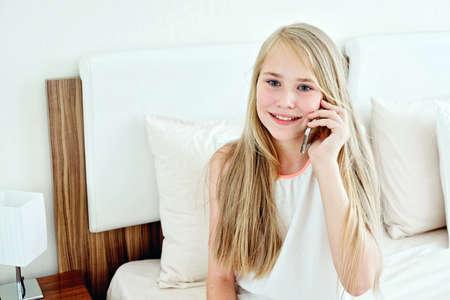 Teenage Girl Lying On Bed Using A Mobile Phone