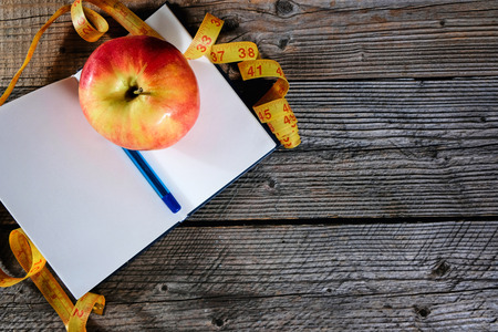 Planning of a diet. A notebook c an inscription - the Diet, a measuring tape, an apple and pen, copyspace. Stok Fotoğraf