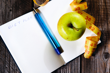 Blank open notebook with green apple and yellow centimeter tapeand pen. Concept sport, diet, fitness, healthy eating. Top view.