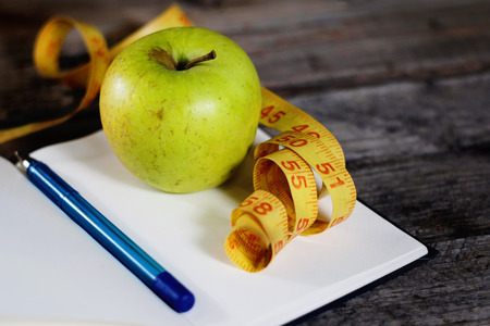 Diet plan, empty notebook, pencil, green apple and measuring tape, flat lay on wooden background. Closeup. Stock Photo
