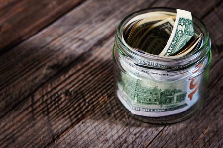 Banconote in dollari in un barattolo di vetro su fondo di legno. Risparmiare denaro concetto