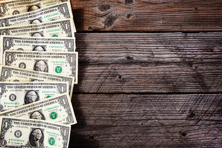 Frame of one dollar bills on a wood background. View from above. Stock Photo