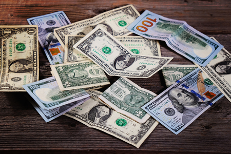 Dollar bills on the wooden table. Financial background. Closeup. Stock Photo