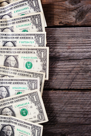 Frame of one dollar bills on a wood background. View from above, copyspace