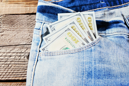A one hundred dollar notes in the front pocket of denim trousers