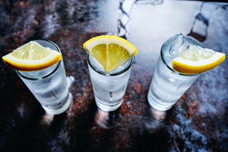 Vodka or gin or tequila in shot glasses on stone table