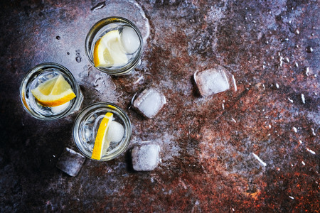 Vodka. Shots, glasses with vodka with ice .Dark stone background.Copy space .Selective focus Stock Photo