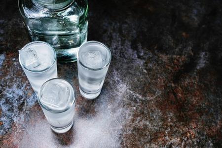 Wodka. Schüsse, Gläser mit Wodka mit Eis. Dunkler Steinhintergrund. Platz kopieren. Selektiver Fokus Standard-Bild