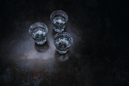 Empty shot glasses on bar counter, top view, copyspace