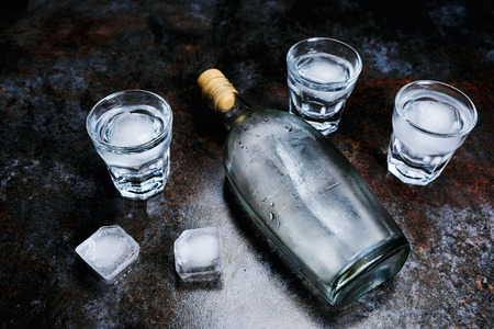 Bottle of vodka with shot glasses and ice. On stone background.