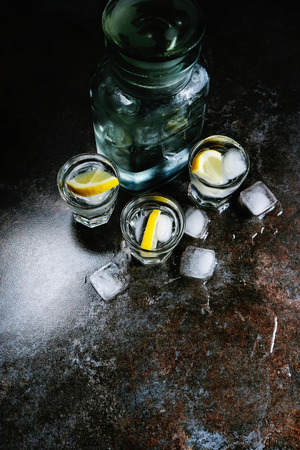 Vodka. Shots, glasses with vodka and lemon with ice .Dark stone background. Vertical image.