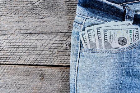 A one hundred dollar notes in the front pocket of denim trousers Stock Photo