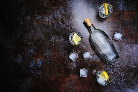 Cold vodka in shot glasses with lemon on stone background. Top view, copy space. Stock Photo