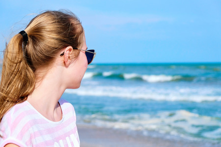 Young and beautiful girl looking far away at sea. Photo from behind